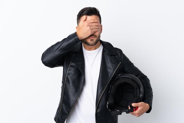 Mann mit einem motorradhelm, der augen durch hände bedeckt