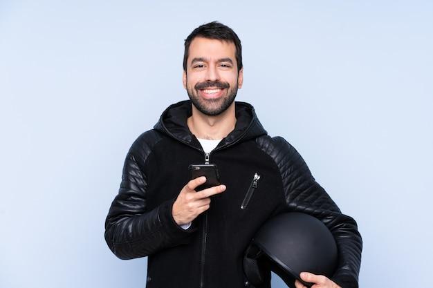 Mann mit einem motorradhelm, der eine nachricht mit dem handy sendet
