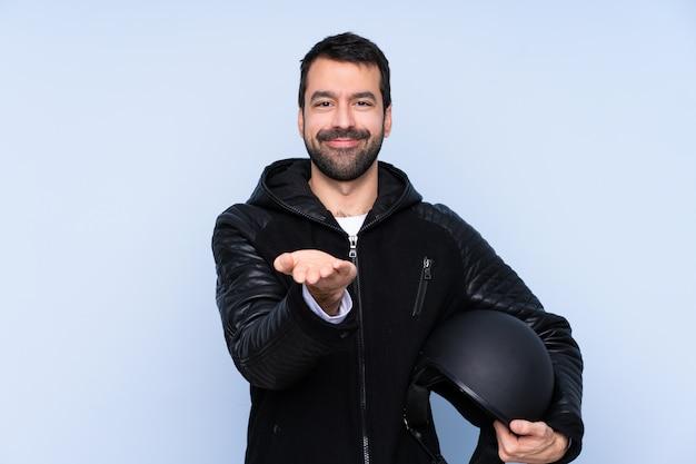 Mann mit einem motorradhelm, der imaginären copyspace auf der handfläche hält, um eine anzeige einzufügen