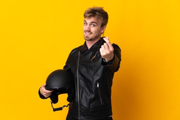 Mann mit einem motorradhelm lokalisiert auf gelbem hintergrund, der geldgeste macht