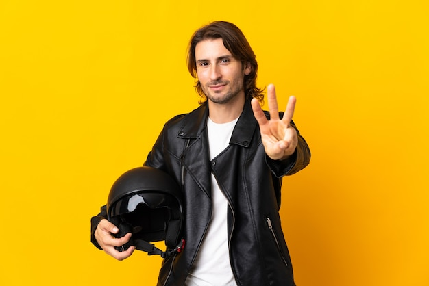 Mann mit einem motorradhelm lokalisiert auf gelbem hintergrund glücklich und zählt drei mit den fingern