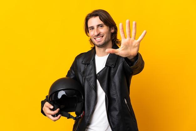 Mann mit einem motorradhelm lokalisiert auf gelbem zählen fünf mit den fingern