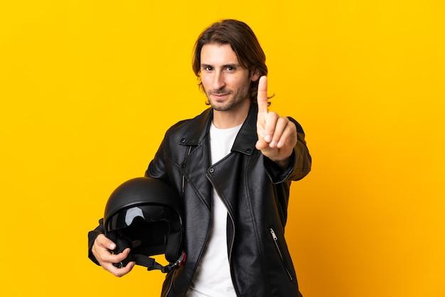 Mann mit einem motorradhelm lokalisiert auf gelbem zeigen und anheben eines fingers