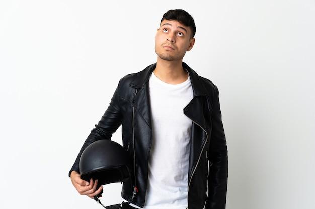 Mann mit einem motorradhelm lokalisiert auf weiß und nach oben schauend
