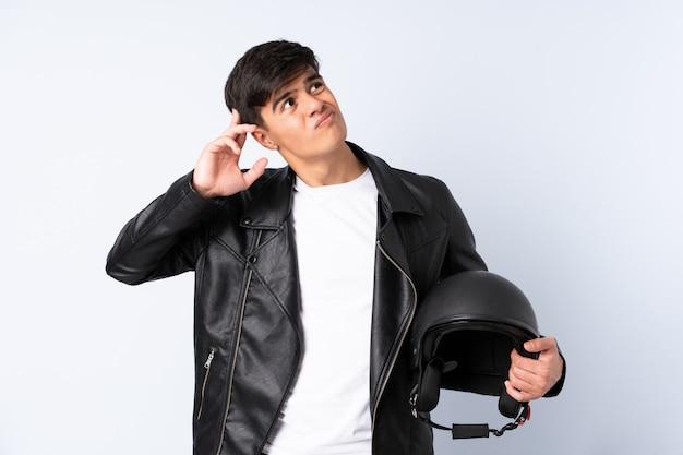 Mann mit einem motorradhelm über blauer wand, die zweifel und mit verwirrendem gesichtsausdruck hat