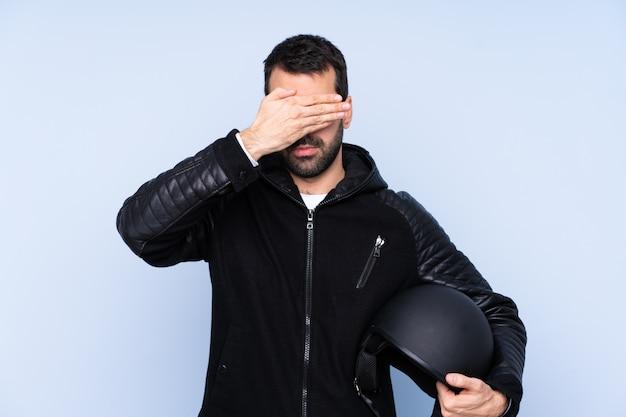 Mann mit einem motorradhelm über isolierten wandbedeckungsaugen durch hände. ich will nichts sehen