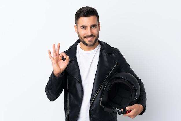Mann mit einem motorradsturzhelm, der ein okayzeichen mit den fingern zeigt