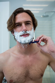 Mann mit einem rasiermesser, um seinen bart zu rasieren