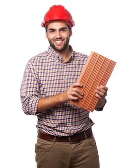 Mann mit einem roten helm und einem ziegelstein
