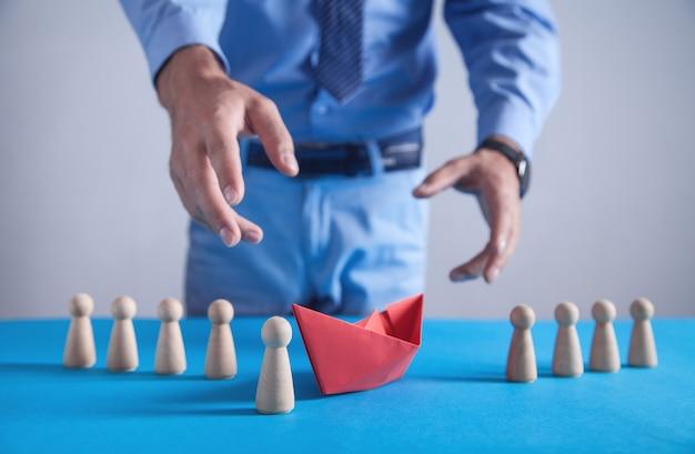 Mann mit einem roten origami-papierboot und menschlichen holzfiguren. geschäft, führung