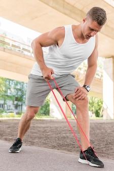 Mann mit einem roten stretching band