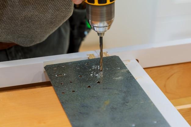 Mann mit einem schraubendreher in der hand wird mit selbstschneidenden blechen aus metallprofil verschraubt