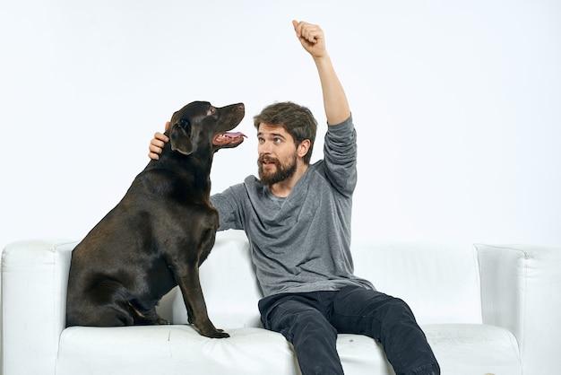 Mann mit einem schwarzen hund auf einem sofa