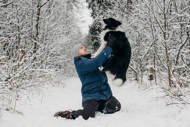 Mann mit einem schwarzen und weißen border-collie-hund im schnee