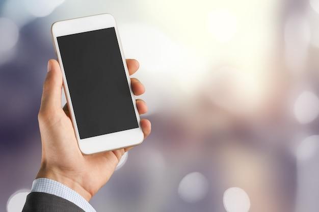 Mann mit einem smartphone auf bokeh-hintergrund