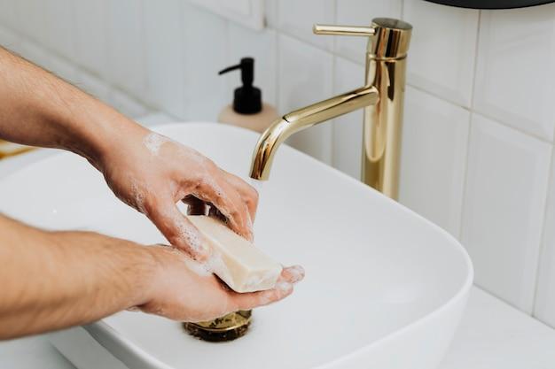 Mann mit einem stück seife, um seine hände zu waschen