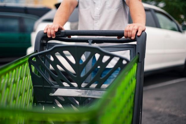 Mann mit einem supermarktwagen auf dem parkplatz