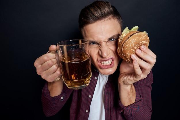 Mann mit einem tablett junk food: hamburger und pommes frites, bier