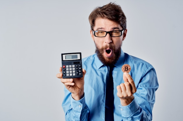 Mann mit einem taschenrechner in den händen kryptowährungs-finanzmanager für elektronisches geld