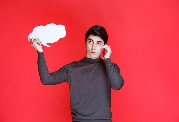 Mann mit einem thinkboard der wolkenform, das mit dem telefon spricht