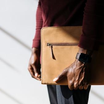 Mann mit einer armbanduhr, die eine soziale vorlage für eine braune aktentasche hält
