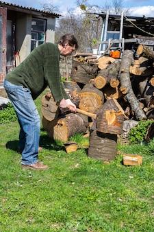 Mann mit einer axt, der einen baumstamm im hinterhof hackt, brennholz für den winter