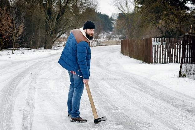 Mann mit einer axt, die auf eine schneebedeckte landstraße geht