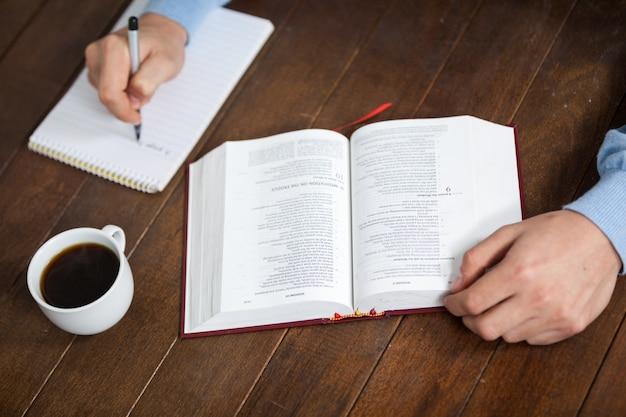 Mann mit einer bibel, die auf notizblock schreibt