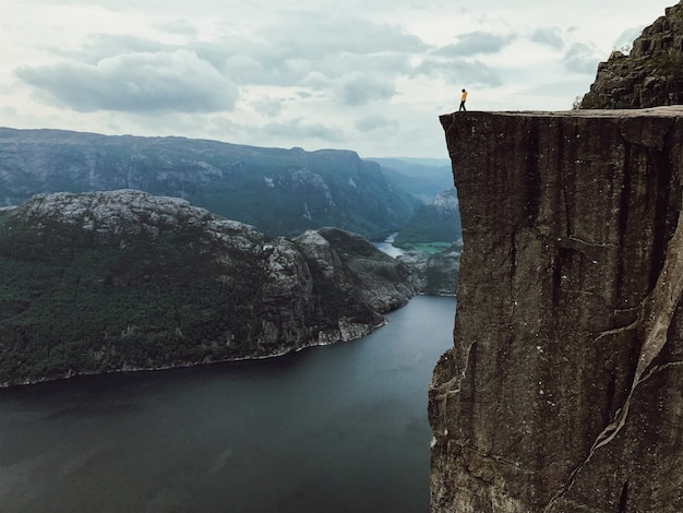 Mann mit einer gelben jacke posiert auf der oberseite des felsens