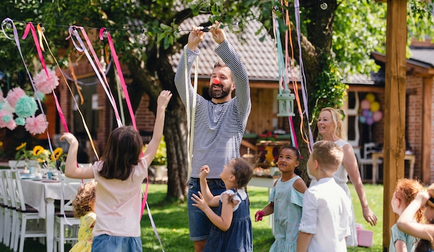 Mann mit einer gruppe von kindern auf der geburtstagsfeier, die im sommer draußen im garten spielt, feierkonzept.