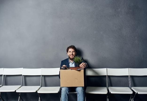 Mann mit einer kiste sitzt nach der entlassung auf einem stuhl mit dingen und dokumenten