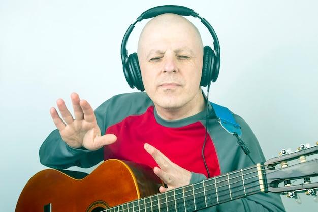 Mann mit einer klassischen gitarre und kopfhörern auf dem kopf, der musik hört