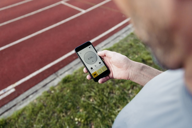 Mann mit einer laufenden app im smartphone.