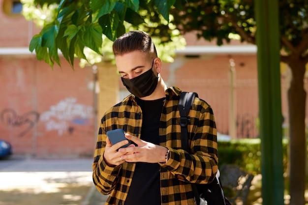 Mann mit einer maske schreibt eine massage mit seinem smartphone