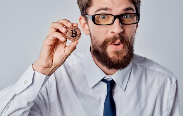 Mann mit einer münze in der hand erfolg freude kryptowährung bitcoin grauer hintergrund copy space