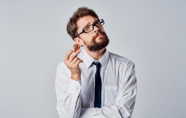 Mann mit einer münze in seinen händen auf einem grauen hintergrund beschnittene ansicht der bitcoin-kryptowährung. hochwertiges foto