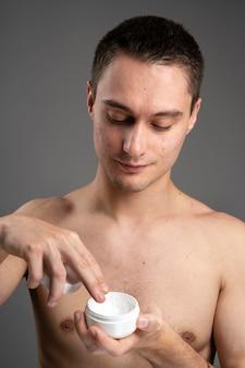 Mann mit einer speziellen creme für akne