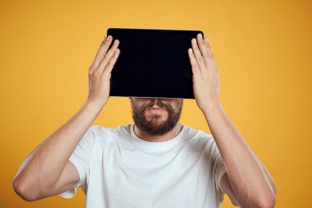 Mann mit einer tablette auf einem gelben hintergrund in einem weißen t-shirt-touchscreen-touchpad des geschäftsmanns der neuen technologien. hochwertiges foto