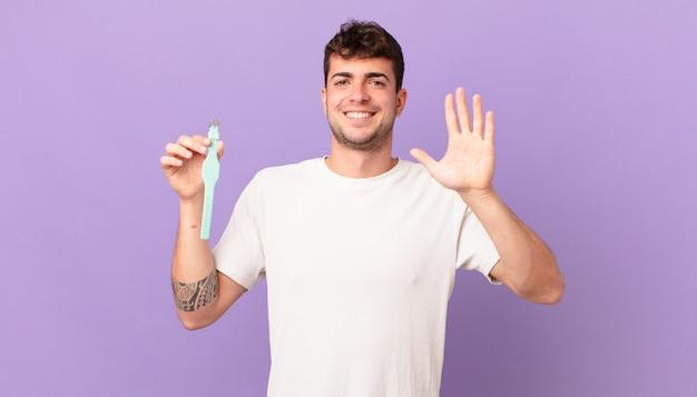 Mann mit einer uhr, die lächelt und freundlich aussieht, die nummer fünf oder fünf mit der hand nach vorne zeigt und herunterzählt