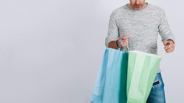 Mann mit einkaufstüten und platz auf der linken seite