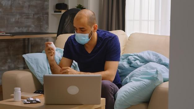 Mann mit einwegmaske, der in einer videokonferenz mit seinem arzt während der coronavirus-quarantäne auf pillen zeigt.