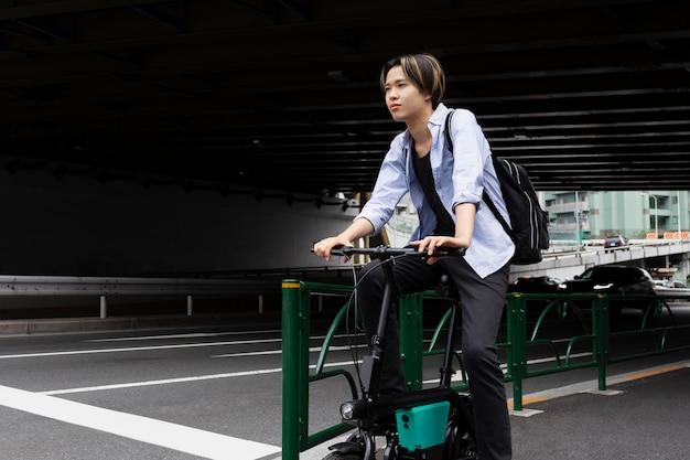 Mann mit elektrofahrrad in der stadt