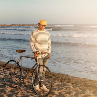 Mann mit fahrrad am meer