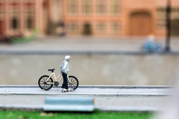 Mann mit fahrrad auf stadtstraße, miniaturszene im freien, europa. mini figuren mit hoher entkalkung von objekten, realistisches diorama, spielzeugmodell