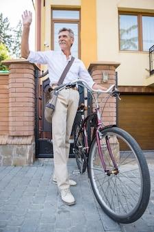 Mann mit fahrrad in der straße, die nachbarn guten tag sagt.