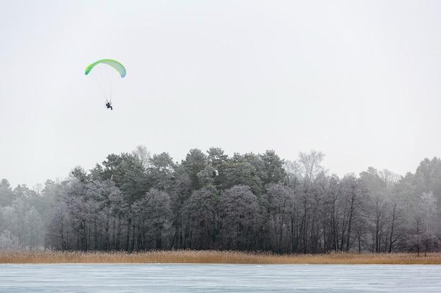 Mann mit fallschirmgleitschirmfliegen hoch in der luft über raureifbäumen und gefrorenem see