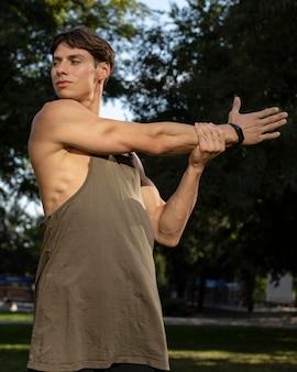 Mann mit fitnessband, das in der natur arbeitet