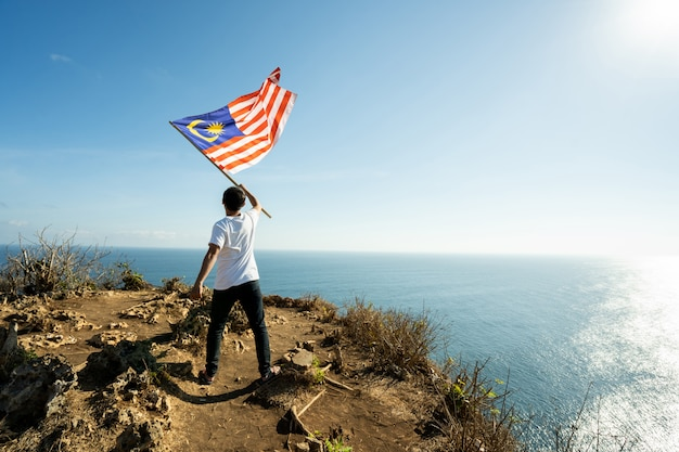 Mann mit flagge von malaysia oben auf berg