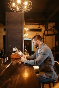 Mann mit flasche alkohol am hölzernen bar counte