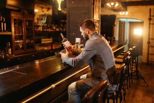 Mann mit flasche alkoholgetränke trinkt am hölzernen bartheke. kundenfreuden in der kneipe, männliche person entspannen im restaurant